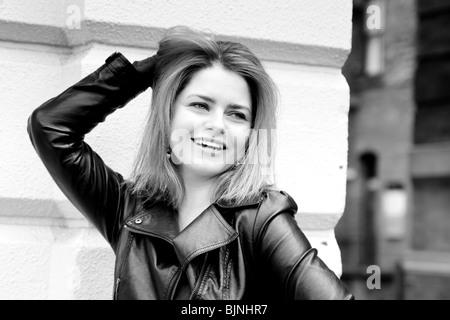 Donna bionda sorridente di una mano i suoi capelli, posa
