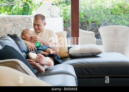 Padre e figlio seduti sul divano Foto Stock