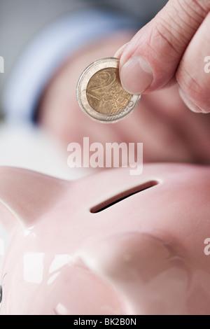 Mettendo mano moneta nel salvadanaio Foto Stock