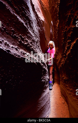 Ragazza spremitura attraverso si restringe di Spooky Gulch, Escalante Canyons, Scalone Escalante National Monument, Foto Stock