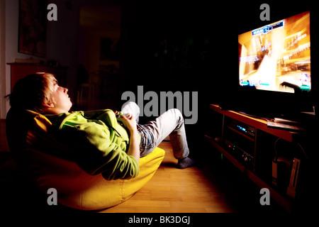 Il ragazzo, 15 anni, giocando un online xbox. gioco utilizzando un grande schermo piatto Foto Stock