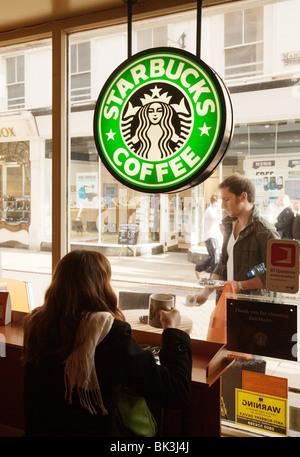 Una ragazza seduta nella finestra di Starbucks di bere caffè, Cambridge, Regno Unito Foto Stock