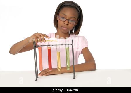 Ragazza di 10 anni, studente, facendo un esperimento scientifico con bicchieri riempiti con liquido colorato. Foto Stock
