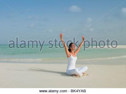 Donna sulla spiaggia seduti con le gambe incrociate con le braccia sollevate Foto Stock