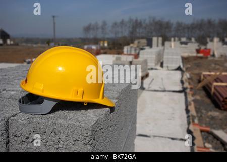 Elmetto seduto su una pila di brezza edificio in calcestruzzo blocchi sul fermo costruzione dell'edificio sito in Foto Stock