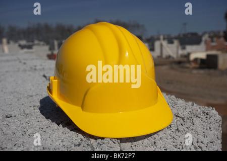 Elmetto seduto su una pila di brezza edificio in calcestruzzo blocchi sulla costruzione dell'edificio sito in Irlanda Foto Stock