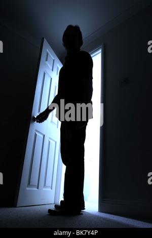 Silhouette di un maschio di entrare in una stanza buia con un albero di luce dietro Foto Stock