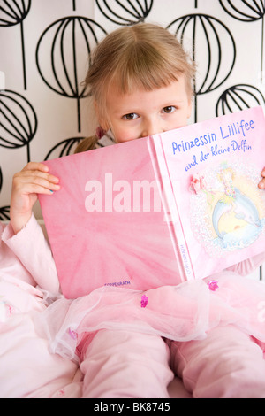 Ragazza nella sua camera da letto con un libro in mano Foto Stock