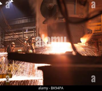 Lavoratori colata di acciaio fuso in una pianta Foto Stock