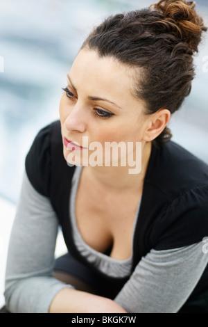 La donna caucasica seduti all'aperto e guardando lontano Foto Stock