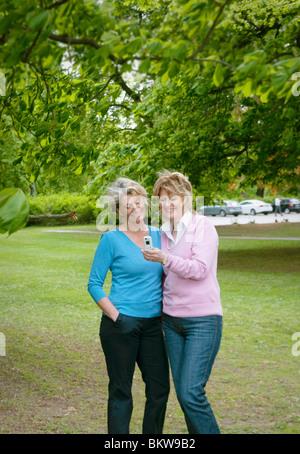 Due donne e un telefono cellulare Foto Stock