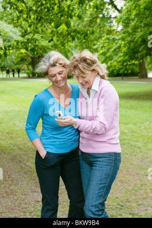 Due amici e un telefono cellulare Foto Stock