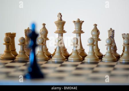 Scacchi, re nero nella parte anteriore del bianco pezzi di scacchi sulla scacchiera