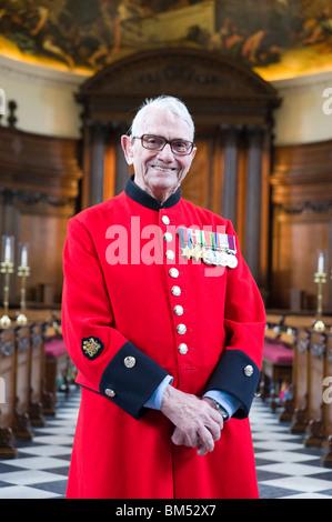 Ritratto di Giovanni In-Pensioner Ley vestito nella sua scarlet ricoprire nella cappella del Royal Hospital Chelsea Foto Stock