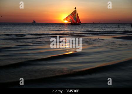 Una imbarcazione a vela passa il tramonto sulla spiaggia bianca, Boracay, la più famosa destinazione turistica nelle Foto Stock