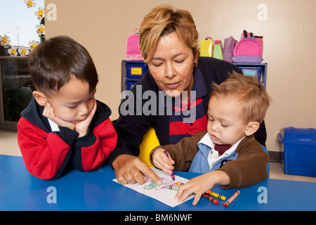 Fort Lauderdale, Florida, Stati Uniti d'America; un insegnante con due giovani ragazzi colorazione a una tabella Foto Stock