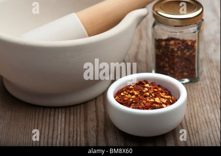 Peperoncino tritato in un piatto bianco, con un mortaio e pestello e contenitore per spezie, su una tavola di legno Foto Stock