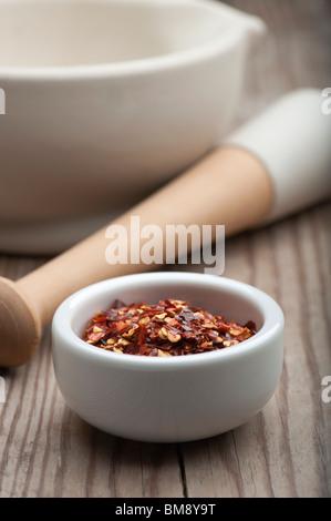Peperoncino frantumato in un piatto bianco, su di un tavolo di legno con un mortaio e pestello in background Foto Stock