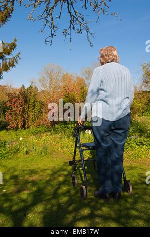 Un modello rilasciato fotografia di una donna anziana con la sua rollator ( a piedi ) telaio in un giardino cottage Foto Stock