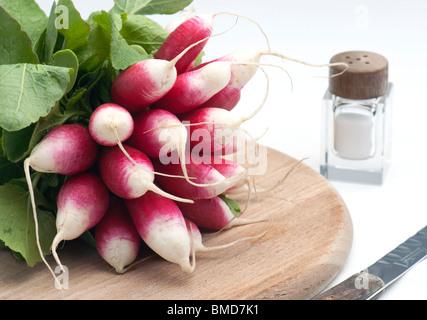 Un mazzetto di fresca prima colazione francese ravanello su un tagliere di legno con un sale di pentola e coltello, Foto Stock