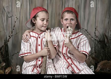Due ragazzi che indossano uniformi di Baseball e uno è di mangiare un cono gelato Foto Stock