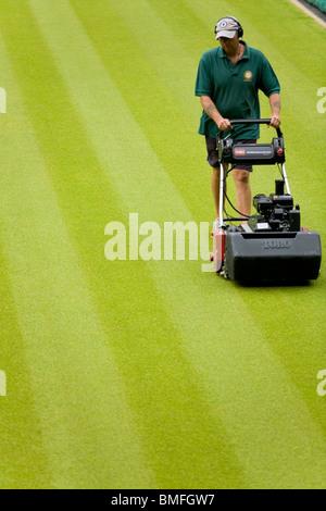 Groundsman tagliare il prato di erba a All England Tennis Club, Wimbledon SW19, Londra. Regno Unito. Foto Stock