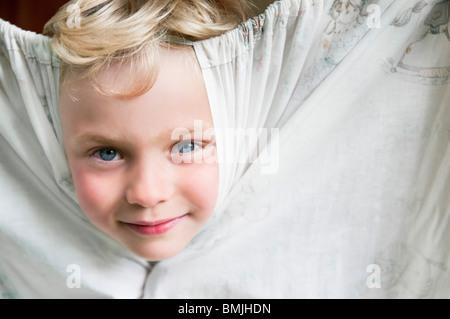 Primo piano sul ragazzo giocando con tendina Foto Stock