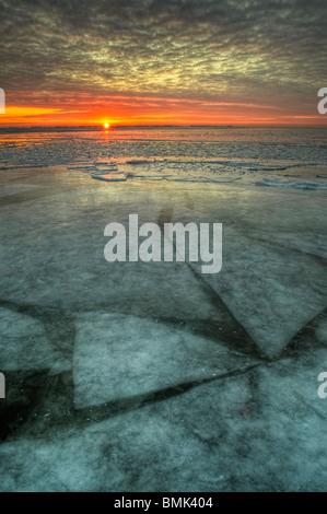 Sunrise attraverso un congelato il lago di acqua dolce nel Michigan, Stati Uniti, America del nord con lo spostamento Foto Stock