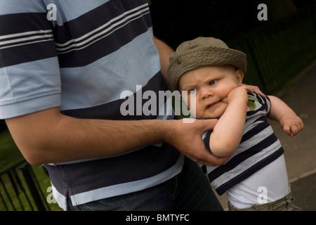 Un undici mese-vecchio bambino viene trattenuto saldamente dal suo papà in un parco pubblico. Foto Stock