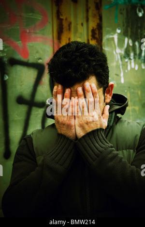 L'uomo faccia nasconde in mani all'aperto Berlino Germania