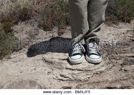 Giovane uomo in piedi sulle rocce, sezione bassa Foto Stock