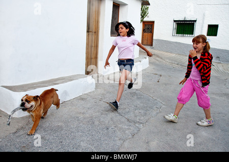 Le ragazze in esecuzione dietro un cane con bastone, Capileira, Andalusia, Las Alpujarras, Spagna