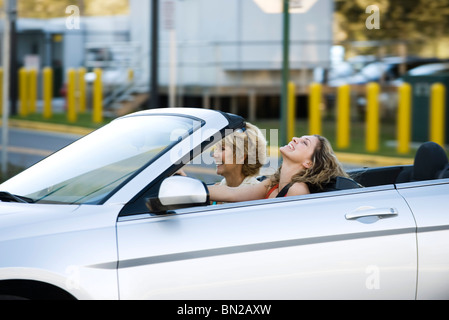 Giovane donna alla guida cabrio, godendo di scampagnata con la madre Foto Stock