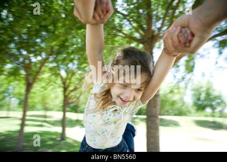 Bambina è oscillata di aria mediante le sue braccia Foto Stock