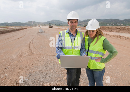 Costruzione di origine ispanica dei lavoratori che utilizzano computer portatile nel campo