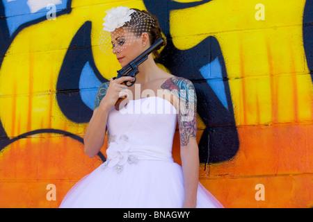 Tatuato sposa contro lo sfondo di graffiti con pistola a mano Foto Stock