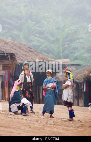 Quattro donne dal Padaung lungo collo della tribù della collina di parlare ad un altro in un villaggio vicino a Foto Stock