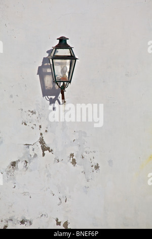 Nero Lanterna di metallo con una forte ombra si trova in un borgo medievale in Europa Foto Stock
