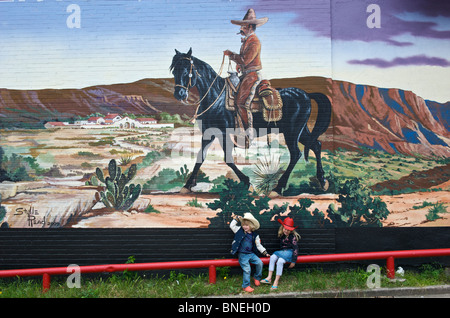 I bambini di fronte a un muro dipinto in Stockyards, Fort Worth, Texas, Stati Uniti d'America Foto Stock