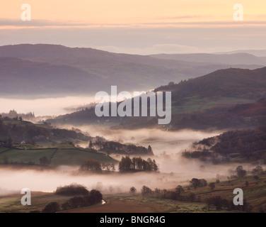 La nebbia indugia nella piccola valle Langdale all'alba, Parco Nazionale del Distretto dei Laghi, Cumbria, Inghilterra. Foto Stock