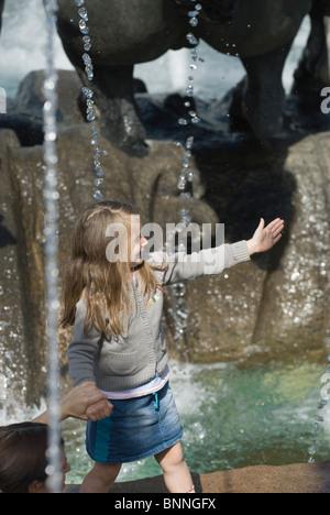 Bambina giocare vicino alla fontana della città Foto Stock