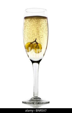 Uva galleggianti in vetro di champagne creando un sacco di bolle Foto Stock