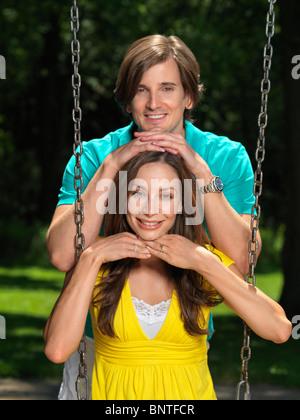 Giovane coppia felice nei loro primi anni trenta divertirsi su altalena al parco giochi per bambini Foto Stock