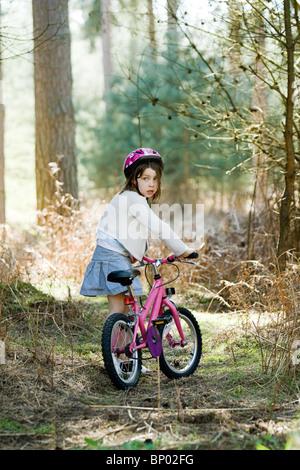Colpo di una giovane ragazza con il suo moto nella foresta Foto Stock