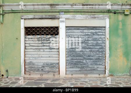 Un dipinto di verde edificio con una porta di metallo griglia visto in questa interpretazione creativa Foto Stock