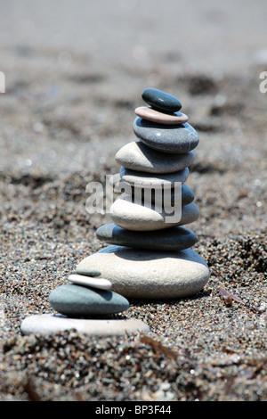 Pietre equilibrato sulla spiaggia di sabbia. Composizione verticale. DOF poco profondo. Foto Stock