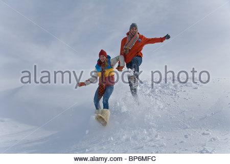 Coppia giovane jumping in neve sul giorno di inverno Foto Stock