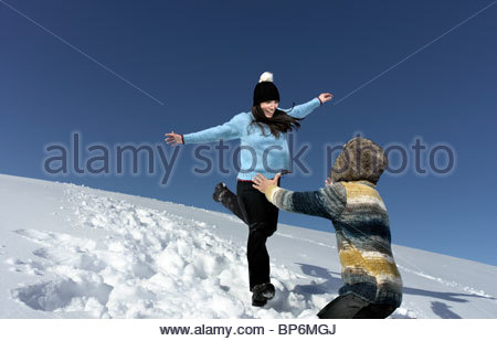 Metà adulto giovane giocare nella neve, uomo donna di cattura Foto Stock