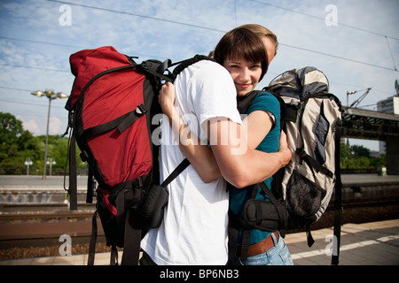 Una giovane donna che abbraccia il suo ragazzo su una piattaforma del treno Foto Stock