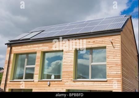 Legname rivestito di carbonio zero casa passiva con finestre con vetri tripli e sul tetto coperto con pannelli solari per l'energia elettrica e di acqua calda